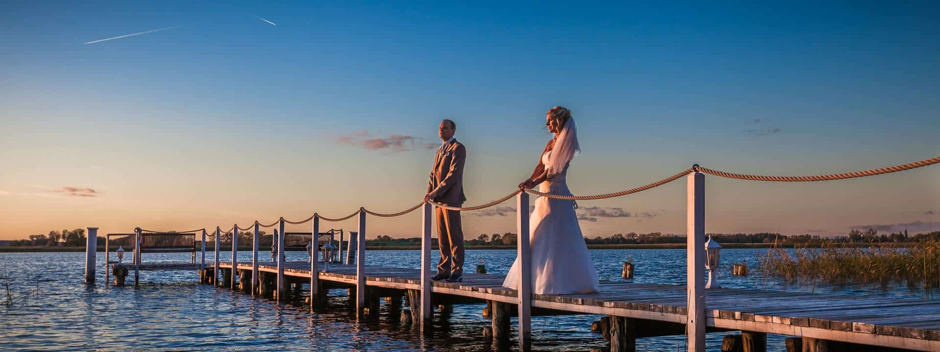Brautpaar-Fotos auf einem Steg zu Sonnenuntergang